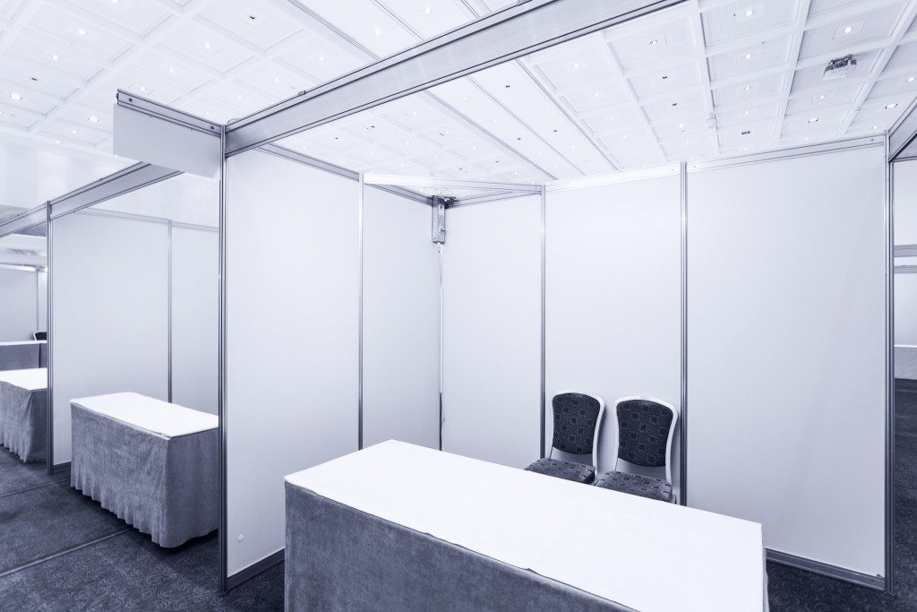 Blank trade show interior with booth and tables