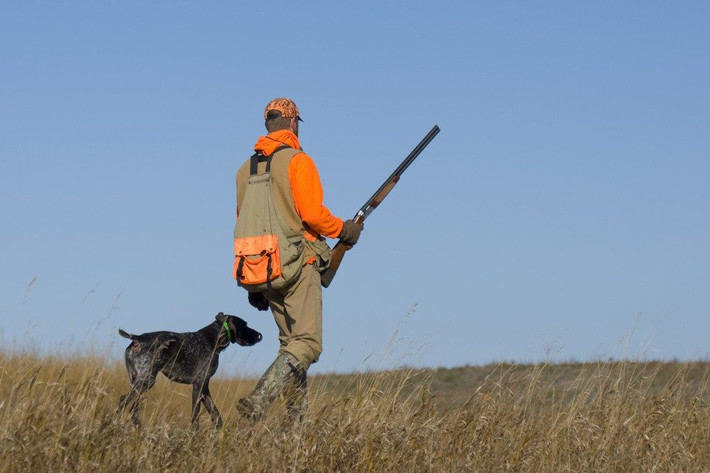 a man holding a gun with a dog