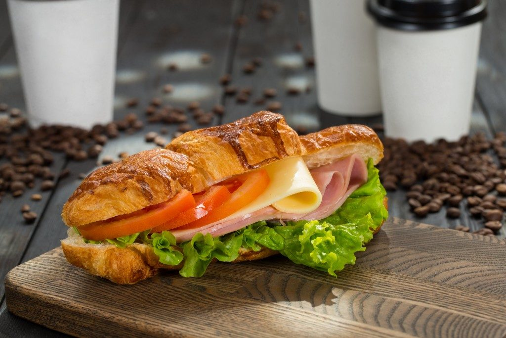 Croissant sandwich with ham, cheese and tomatoes on wooden cutting board.