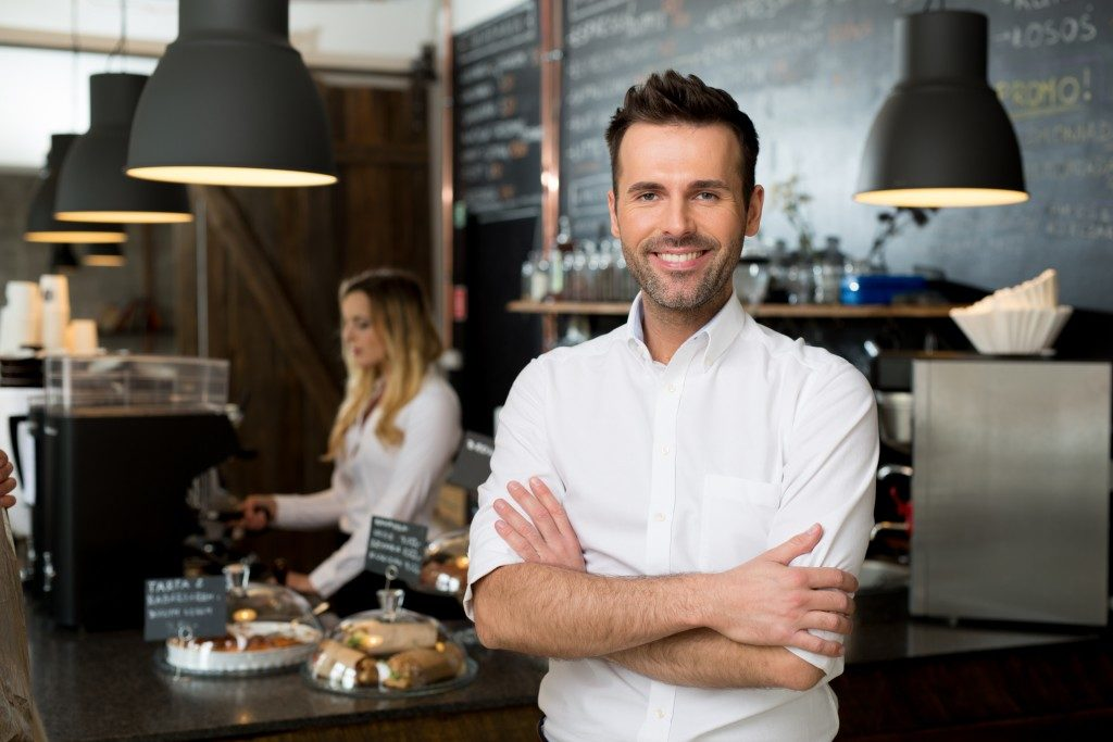 Small business owner standing in front of coffee shop