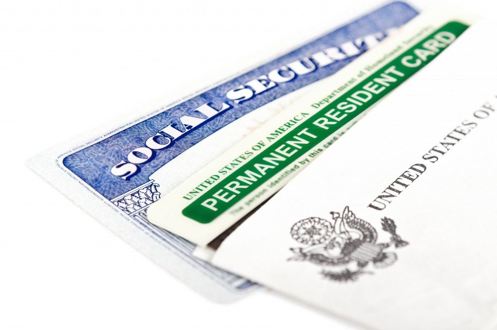 social security and green card on white background. Immigration concept. Closeup with shallow depth of field.