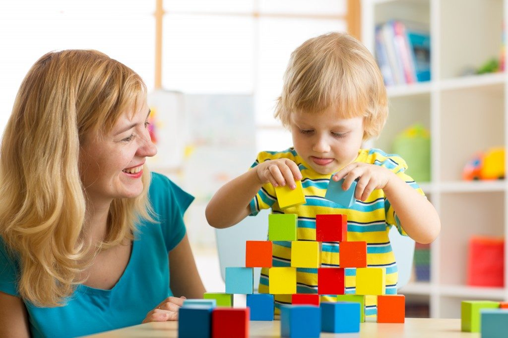 Child boy together with mother playing educational toys
