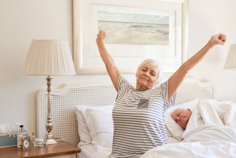 Senior woman sitting on her bed in the morning yawning with arms raised in a stretch with her husband sleeping next to her