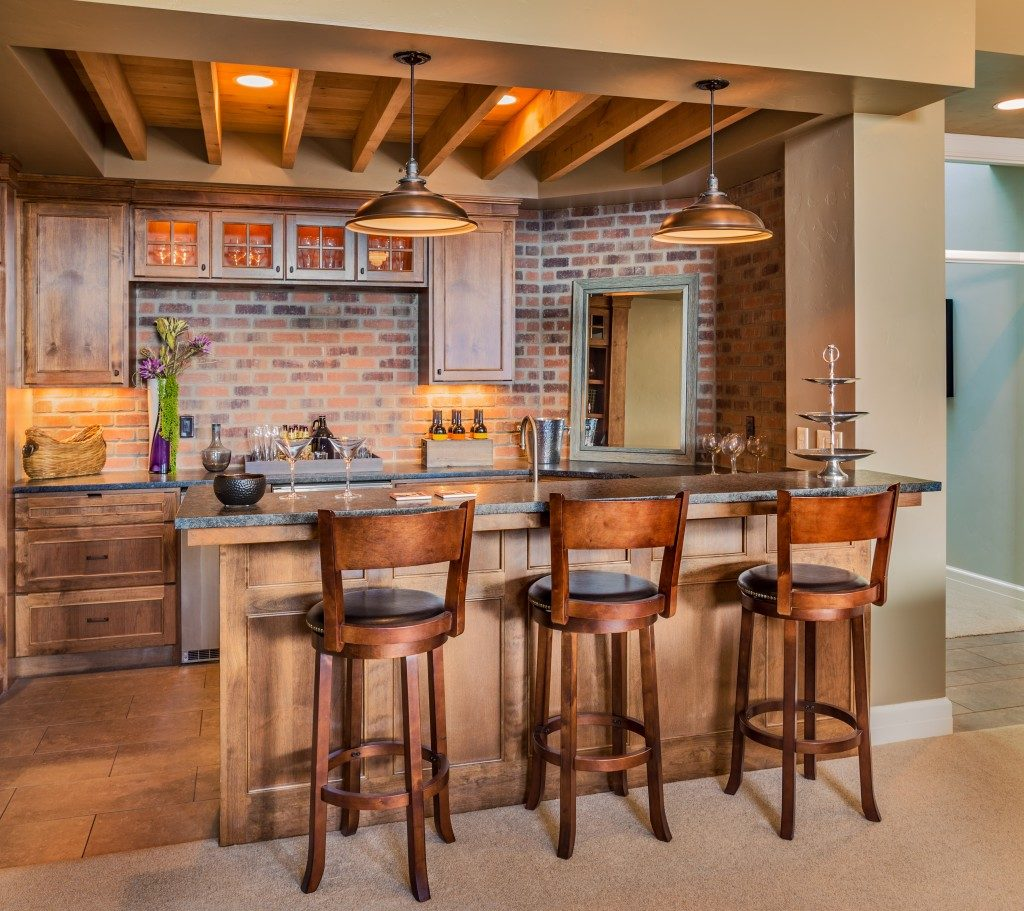 Bar in new luxury home, complete with chairs wine glasses, beer, and new cabinets