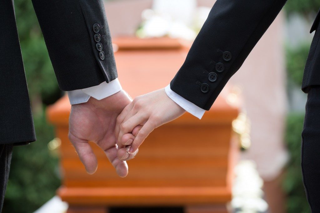 two people holding hands while in a funeral