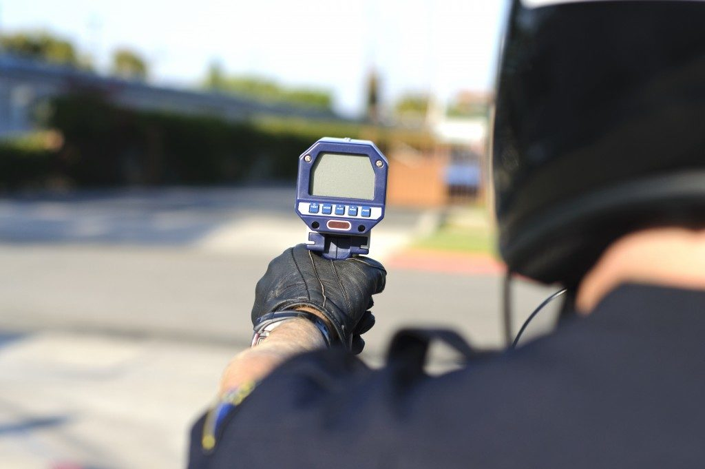 policeman holding and using a radar gun for speed