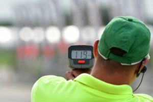 man with earpiece holding a radar gun