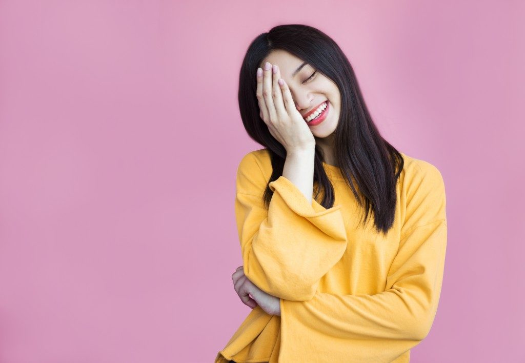 woman smiling covering half of her face