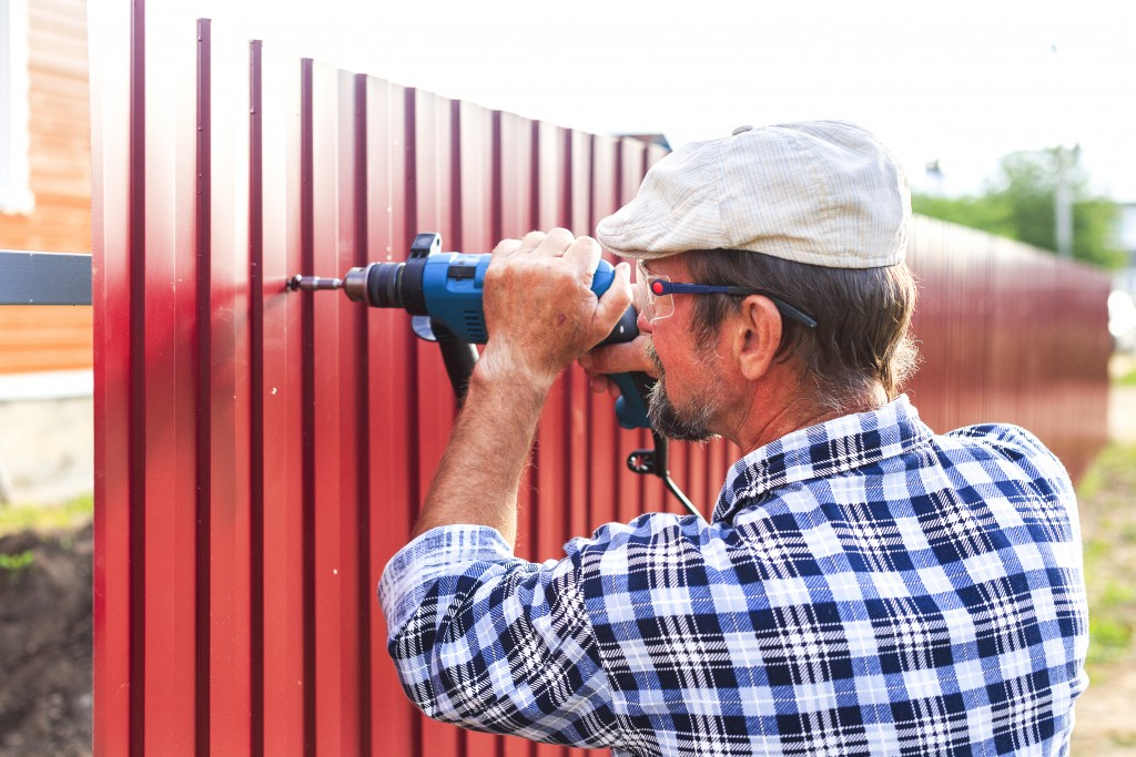 man with a drill builds metal fence