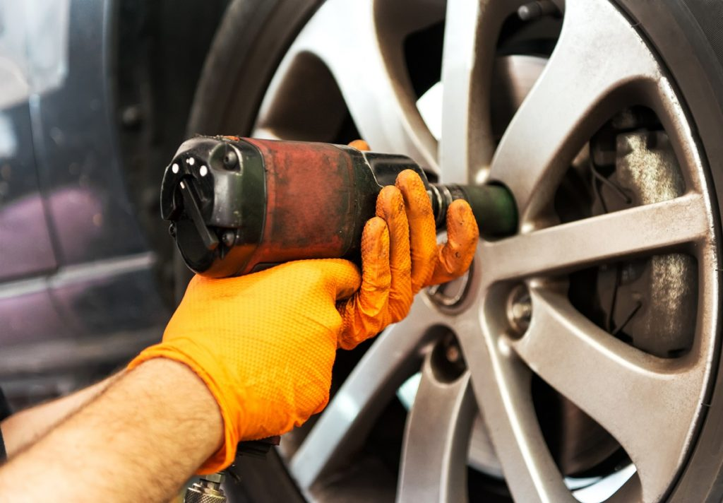 Mechanic unscrewing car wheel with impact wrench