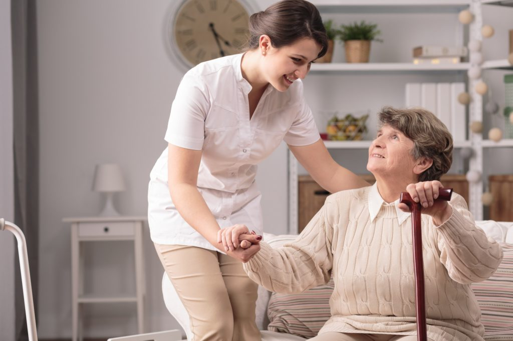 elderly woman assisted by her aud