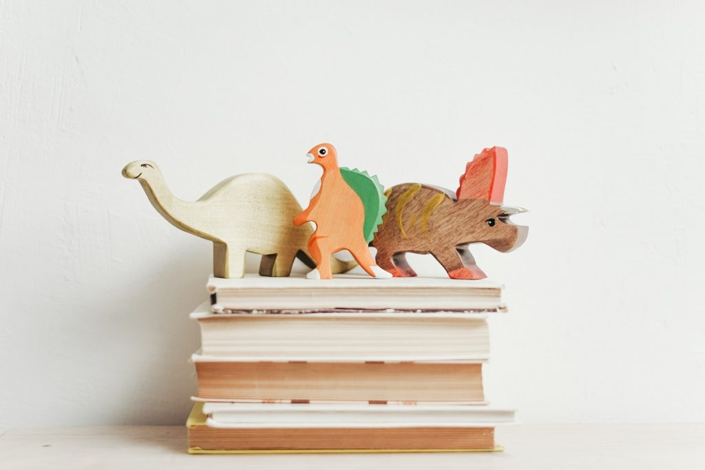 wooden dinosaurs on top of children's books