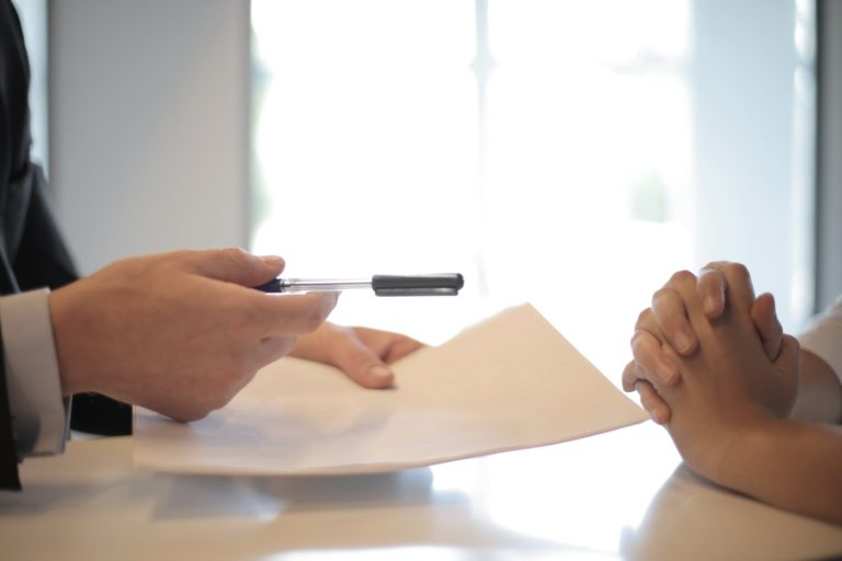 handing over paper and pen