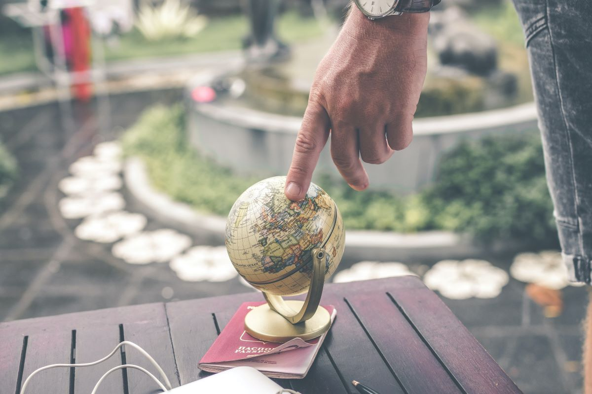 man touching globe with index finger