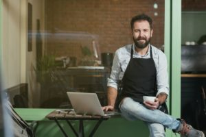cafe owner sitting outside working on laptop holding cup of coffee